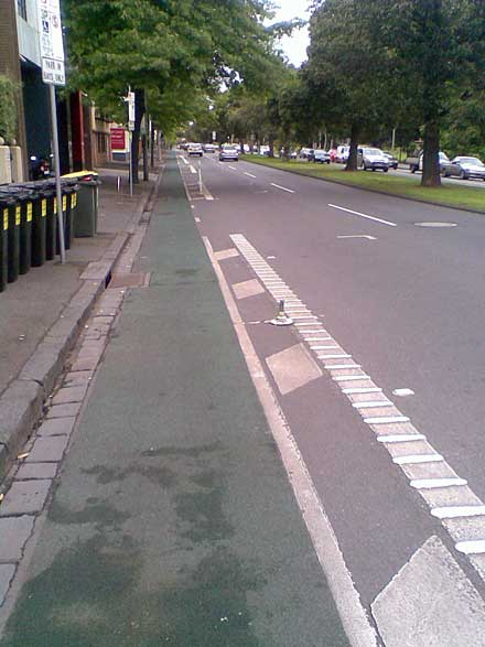 A stretch of the eastbound bike lane on Albert St, East Melbourne, showing a broken pole mounting.