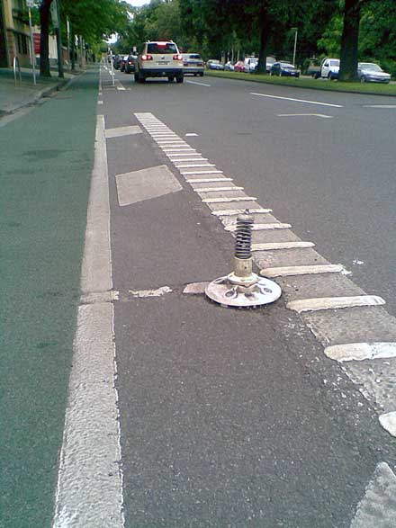 A stretch of the eastbound bike lane on Albert St, East Melbourne, showing a close-up of a broken pole mounting.